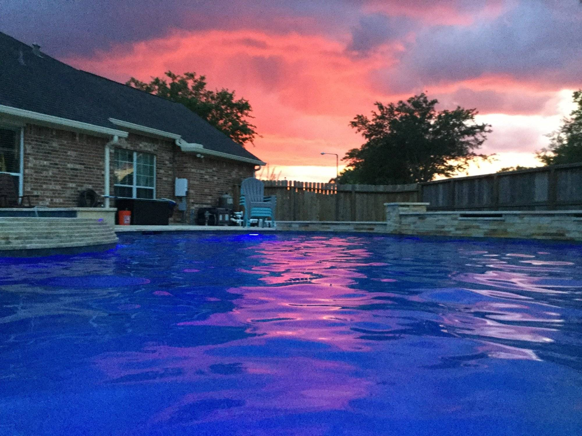 A red sunset over a clear blue swimming pool