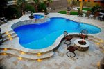freeform-pool-with-raised-spa-with-spillover-travertine-decking-with-lighted-steps-and-fire-pit.jpg